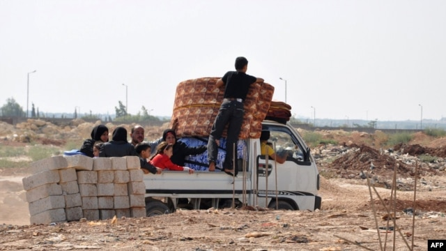 Syrian civilians flee the northern city of Aleppo during a lull in fighting between opposition forces and army troops on July 25.