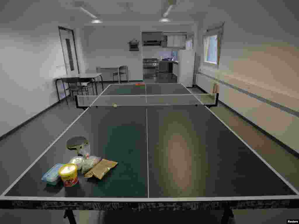 Food is left on a pingpong table in a kitchen in one of the wings of the Detention Unit.