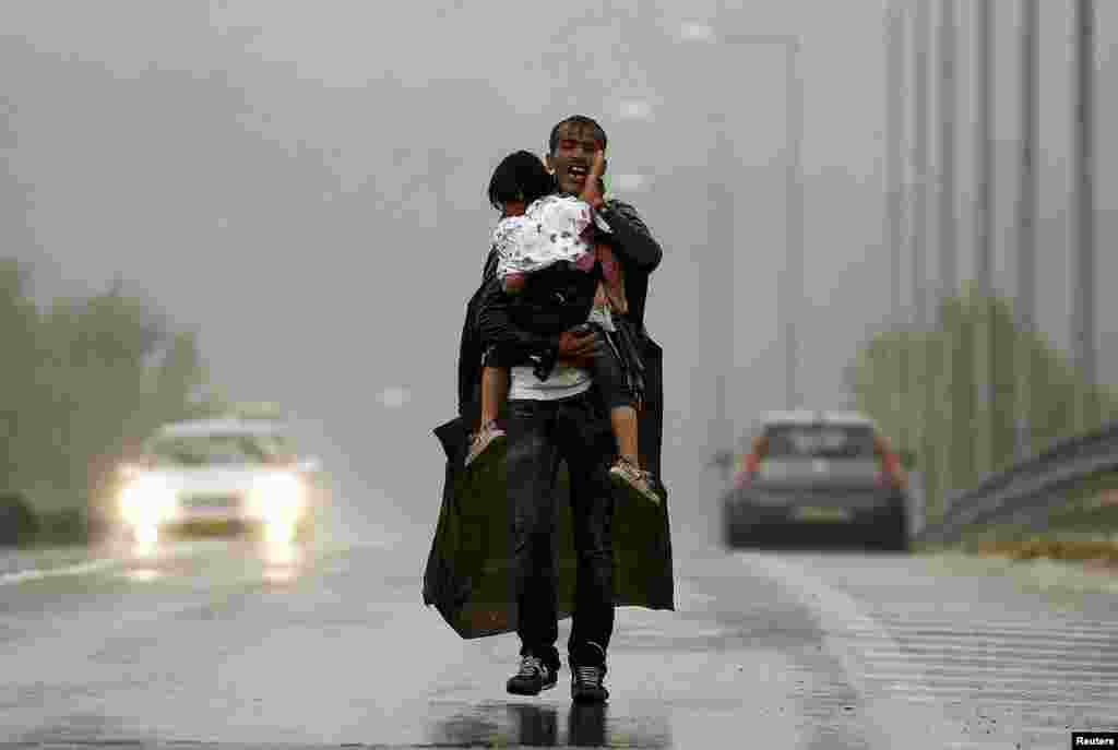 A Syrian refugee screams in frustration as he carries his daughter through a rainstorm toward Greece's border with Macedonia, near the Greek village of Idomeni. (Reuters/Yannis Behrakis)