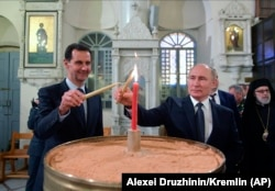 Russian President Vladimir Putin and Syrian President Bashar al-Assad light candles while visiting an Orthodox cathedral for Christmas in Damascus on January 7.