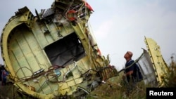 Украинаның көнчыгышына җимерелеп төшкән Боинг 777 очкычының бер кисәге янында тикшерүче