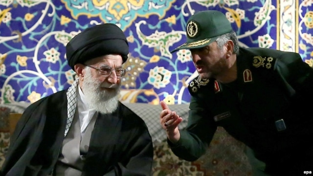Iran's Supreme Leader Ayatollah Ali Khamenei (left) listens to Revolutionary Guards Commander Mohamad Ali Jafari during a ceremony in Tehran last month. Both Khamenei and the Revolutionary Guards are among those with the most to lose if the current system unravels in Iran.