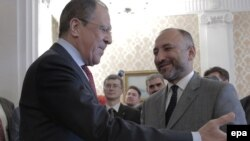 Russian Foreign Minister Sergei Lavrov (L) welcomes Afghan National Security Advisor Hanif Atmar during their meeting in Moscow on April 15.
