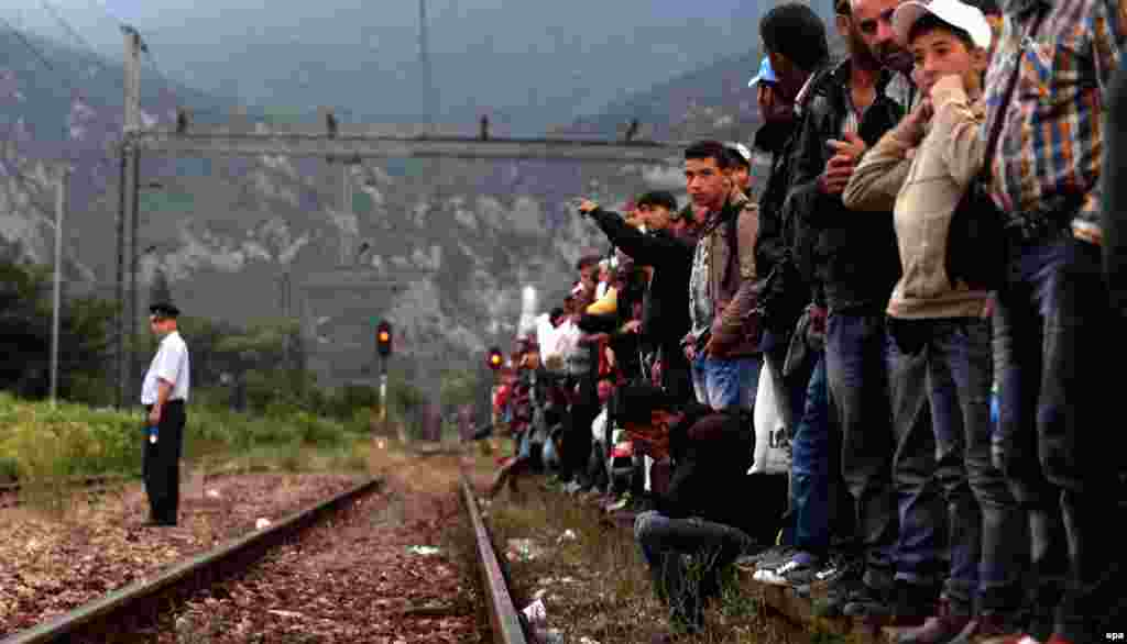 Migrants wait for a train to Serbia on the track near a train station in Demi Kapija,  Macedonia, on June 18. (epa/Nake Batev)
