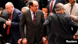 Iraqi Prime Minister Nuri al-Maliki (center) attends a session of parliament in Baghdad on July 1.