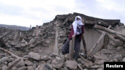 Turkey -- A woman stands on the ruins of a destroyed house in Okcular Village, in Elazig province, 08Mar2010