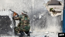 Libya -- A Libyan National Transitional Council (NTC) fighter fires at loyalist troops during a battle in Sirte's neighbourhood Number 2, 19Oct2011
