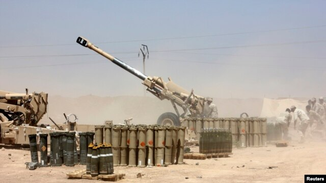 Iraqi security forces fire artillery during clashes with Sunni militants of the Islamic State of Iraq and the Levant (ISIL) on the outskirts of the town of Udaim in Diyala Province on June 22.