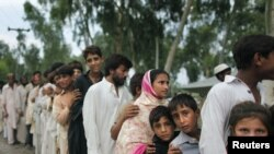 Flood victims jostle for position in a line to receive evening food handouts from a charity at a road-side tent camp near Nowshera, in Khyber Pakhtunkhwa Province.