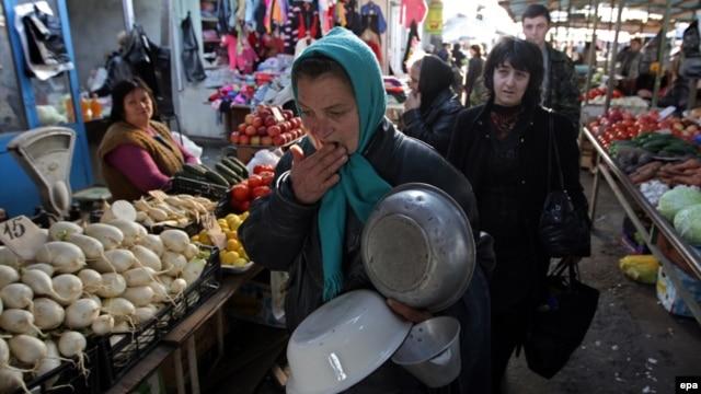 A woman peddles metal basins at a street market in Sukhumi, Abkhazia.