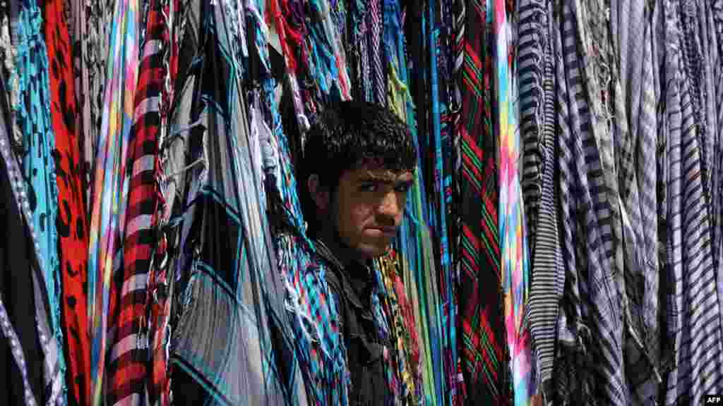 An Afghan scarf vendor waits for custumers in downtown Kabul on May 31. (AFP/Aref Karimi)
