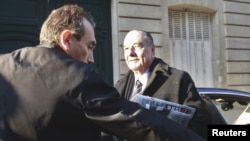 Former President Jacques Chirac arrives at his office in Paris today.