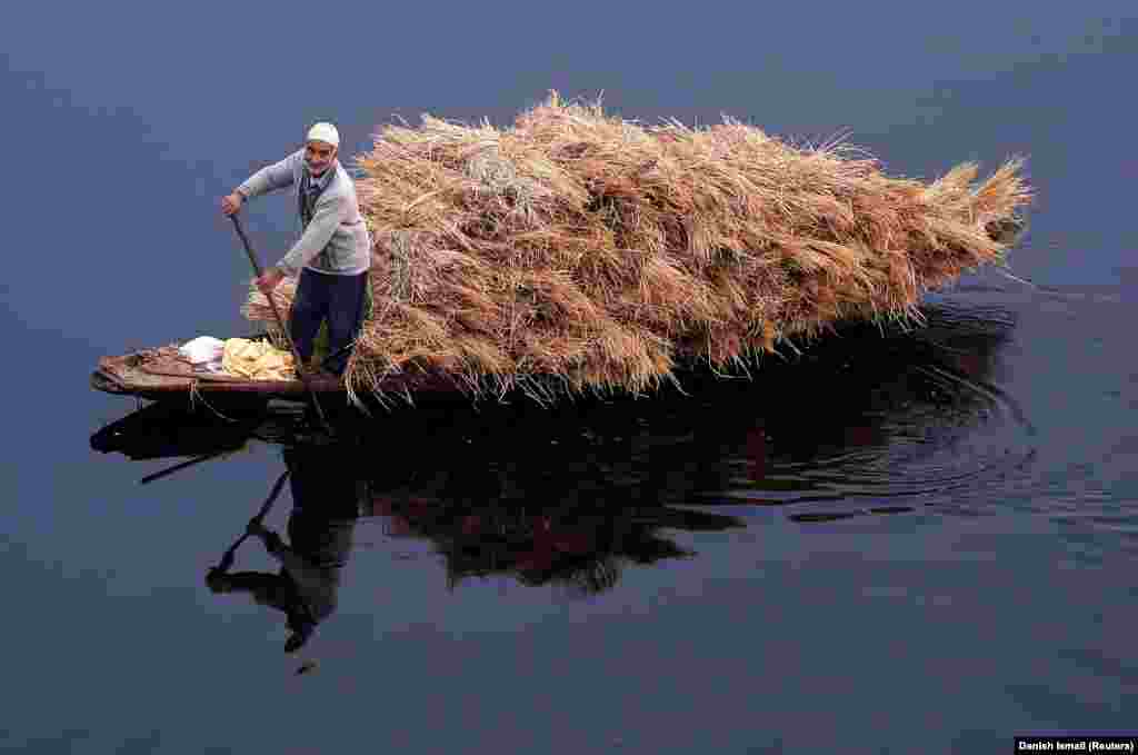A man rows a boat filled with straw on the waters of Nageen Lake on a cold morning in Srinagar, India. (Reuters/Danish Ismail)