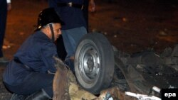 Security officer examines a blast site on a highway near the airport in Mumbai