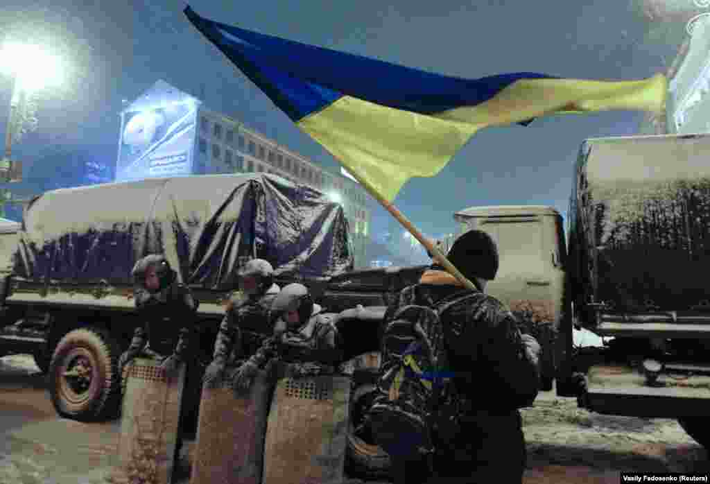A demonstrator holds a Ukrainian flag as he stands next to Interior Ministry personnel in central Kyiv late on December 9.