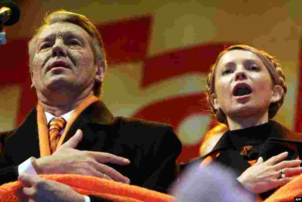 Orange Revolution leaders Viktor Yushchenko (left) and Yulia Tymoshenko sing the national anthem with supporters during the Orange Revolution in December 2004.