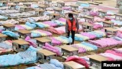 Рабочий среди кроватей, установленных для заражённых коронавирусом. Стадион в Ухани временно переоборудован в больницу. Китай, 4 февраля 2020