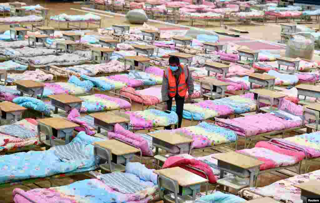 A worker sets up beds at the Hongshan Stadium in Wuhan, which has been converted into a makeshift hospital.