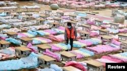Рабочий среди кроватей, установленных для заражённых коронавирусом. Стадион в Ухане временно переоборудован в больницу. Китай, 4 февраля 2020 года.