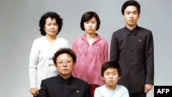 Түндүк Кореянын мурдагы лидери Ким Чен Ир (биринчи катарда солдо) уулу Ким Чен Нам (биринчи катарда оңдо) жана башка туугандары менен. 1996-жыл
