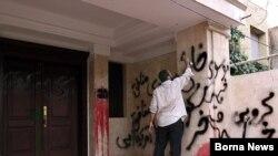 یکی از تجمعکنندگان در حال شعار نویسی بر ضد مهدی کروبی بر روی دیوار خانه وی.