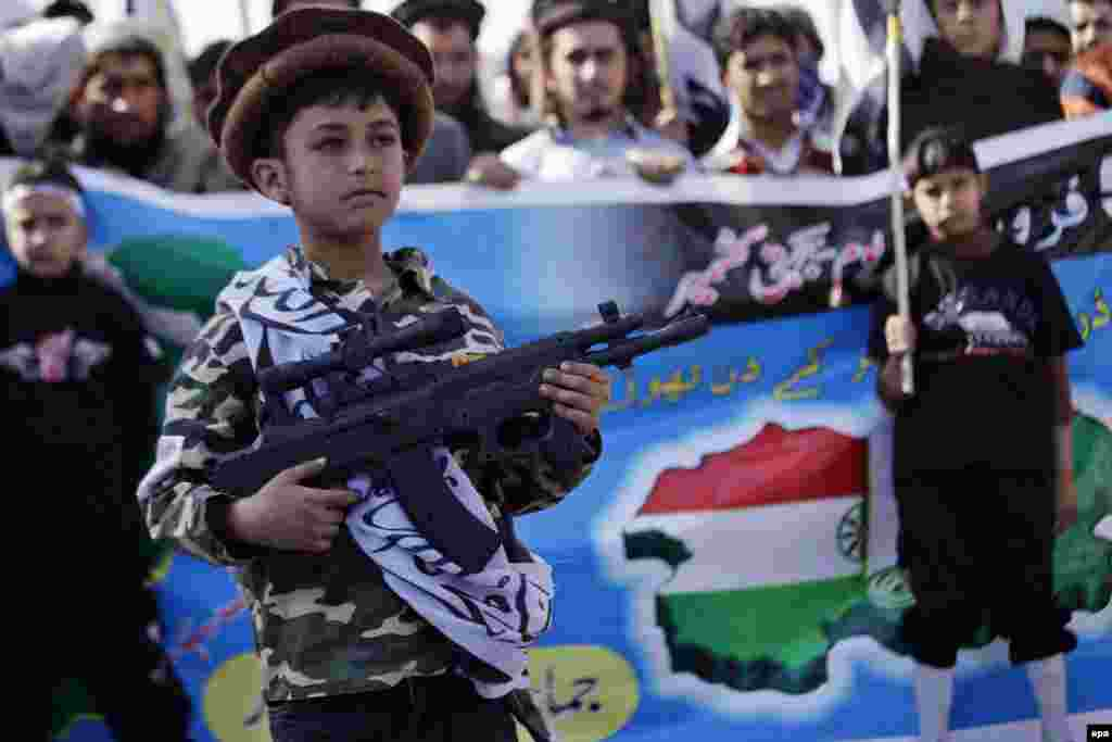 A child supporter of the banned Pakistan-based charity Jamaat-ud-Dawa holds a toy gun during a rally in the Pakistani city of Peshawar expressing solidarity with Kashmiris living in Indian Kashmir. (epa/Arshad Arbab)