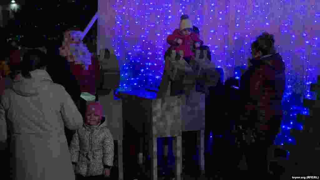 Дети радуются деревянным лошадкам и Деду Морозу