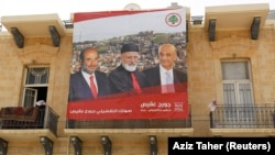LEBANON -- A poster of Samir Geagea, leader of the Christian Lebanese Forces, former Lebanon's Christian Maronite Patriarch Mar-Nasrallah Boutros Sfeir and Lebanese parliament candidate Georges Aqeis hangs on a building in the city of Zahle, May 4, 2018