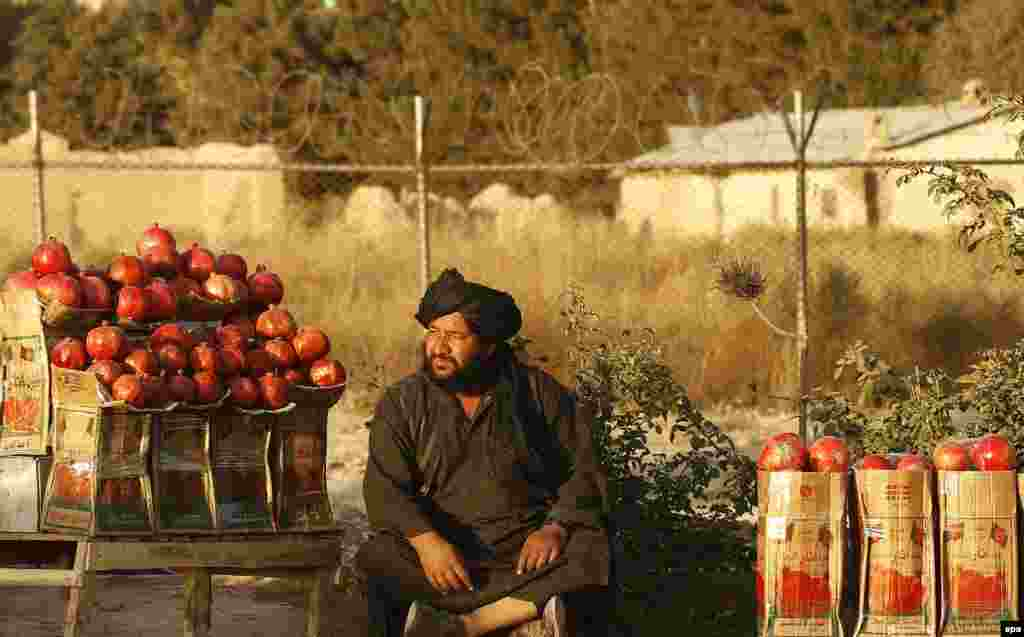 An Afghan man sells pomegranates at a roadside in Kabul. (epa/Jawad Jalali)