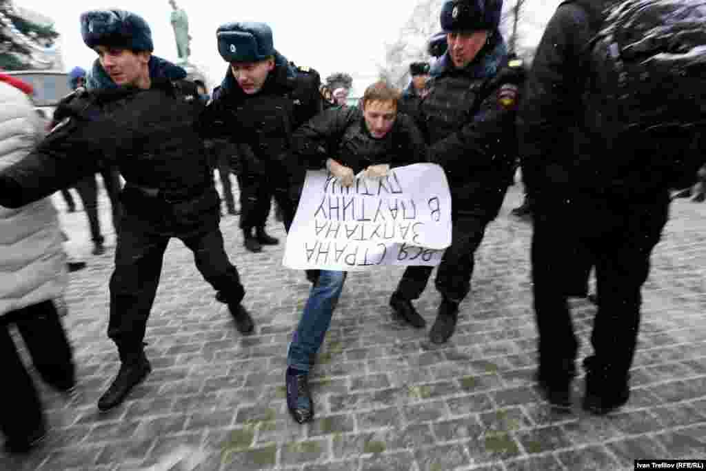 """Задержание активиста на Пушкинской площади Москвы. В руках у него плакат """"Вся страна запутана в паутину Путина"""""""