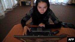Компьютер пайдаланып отырған әйел. Ауғанстан, 22 маусым 2012 жыл. (Көрнекі сурет)