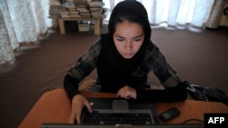A woman browses on a computer at a women-only Internet cafe in Kabul.