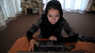 Afghanistan --An ethnic Hazara woman browses the Facebook website on a computer at the Young Women For Change internet cafe, Afghan first women-only net cafe, in Kabul, 22Jul2012