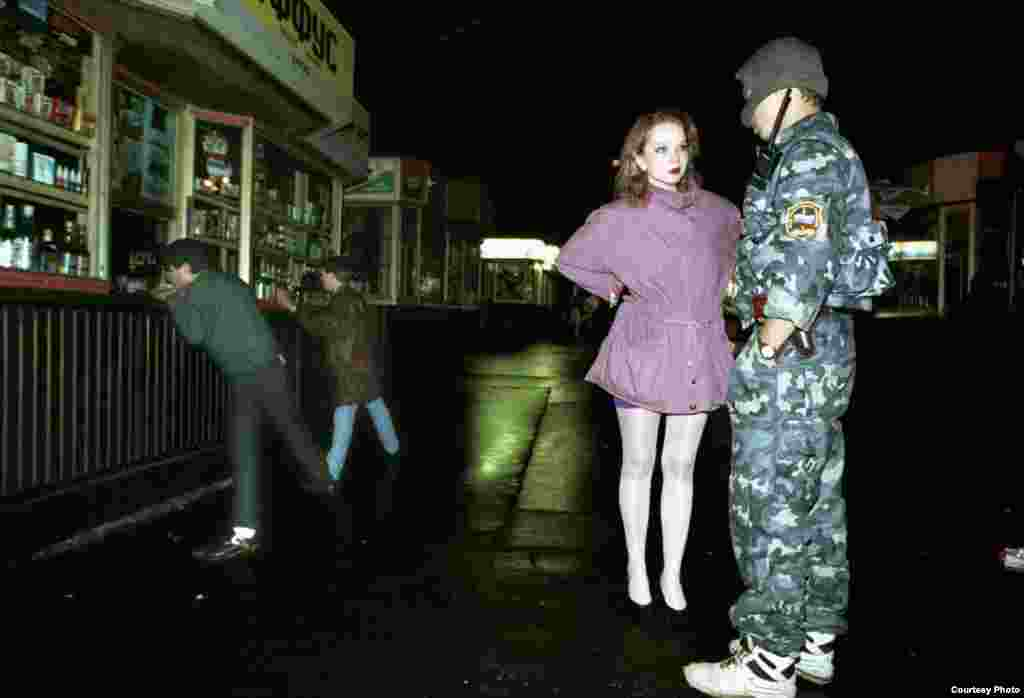 Милиционер проводит воспитательную беседу с девушкой, предварительно поставив ее сутенеров (слева) лицом к витринам киосков на ночной Тверской улице в Москве, 1994.