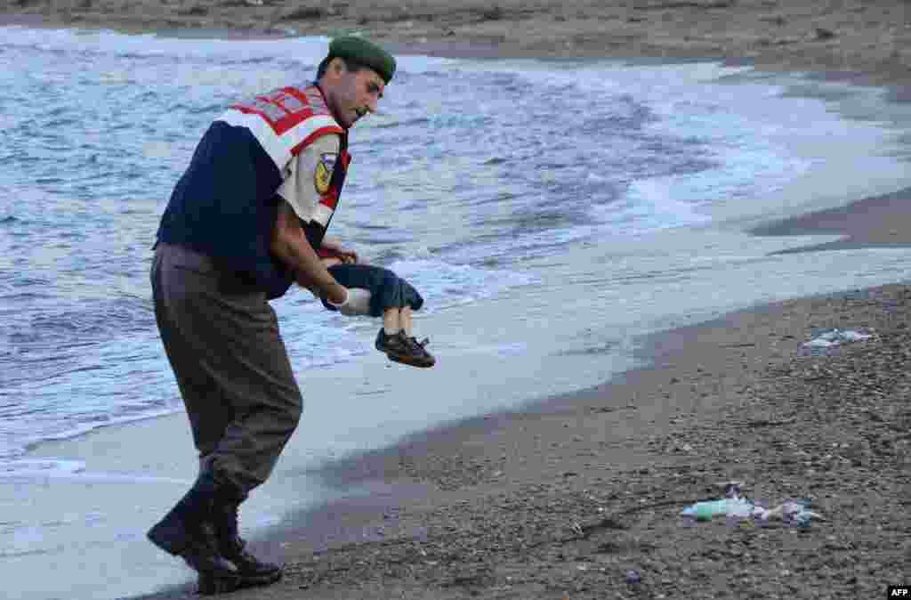 عکس یک نیروی پلیس ترکیه که جسد یک کودک مهاجر را از در جنوب این کشور از آب گرفته است. یک قایق حامی پناهجویان در نزدیکی جزیره ای در یونان روز یازدهم شهریورماه غرق شد