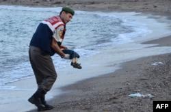 Турецкий полицейский с телом маленького Айлана Курди. 3 сентября