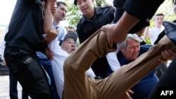 """Полиция қызметкерлері """"Қазақстанның демократиялық таңдауы"""" қозғалысын қолдап шыққан азаматтардың митингісіне кездейсоқ тап болған азаматтардың бірін қамау үшін ұстап жатыр. Алматы, 23 маусым 2018 жыл"""