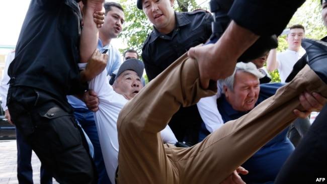 Сотрудники полиции тащат мужчину, который оказался на перекрестке, обозначенном запрещенным в стране движением ДВК как место проведения митинга. Алматы, 23 июня 2018 года.