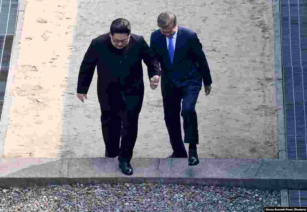 Ким Чен Ынның шекаралық белгі ретінде қойылған бетоннан аттаған сәті.