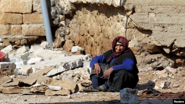A woman rests near rubble in the Syrian town of Darat Izza in Aleppo Province on February 28.