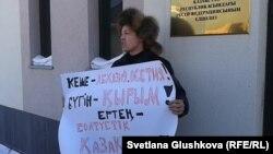 """Гражданский активист Махамбет Абжан держит плакат с надписью: """"Вчера - Осетия и Абхазия, сегодня - Крым, завтра - Северный Казахстан"""" у посольства России в Астане. 3 марта 2014 года."""