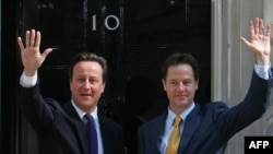 New Prime Minister David Cameron (left) and new Deputy Prime Minister Nick Clegg, wave as they pose for pictures outside 10 Downing Street in London on May 12.