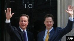 British Prime Minister David Cameron (left) and new Deputy Prime Minister Nick Clegg wave in front of Downing Street.