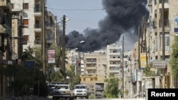 Smoke rises from the El-Edaa district of Aleppo after missiles were launched by a Syrian Air Force fighter jet on September 5.