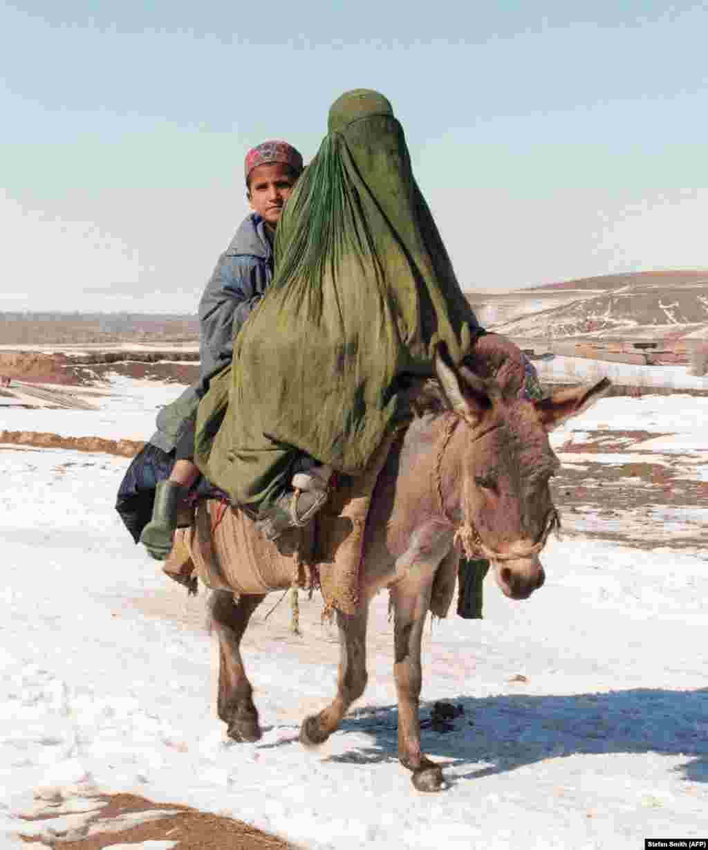 A veiled woman riding a donkey with a young boy. Under Taliban rule, women were required to wear such clothing outside at all times, and could only leave their houses with a male relative.