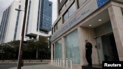 A security guard stands in front of a closed branch of Russian Commercial Bank in Nicosia, Cyprus on March 19.