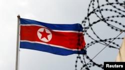 Флаг Северной Кореи на фоне колючей проволоки. Архивное фото.