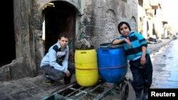 Мальчики, которые возят воду на тележке в сирийском городе Алеппо. 4 января 2017 года.