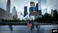 A U.S. flag is placed on the 9/11 memorial before the ceremony to commemorate the 14th Anniversary of the terrorist attacks in New York, September 11, 2015.