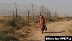 Женщина проходит вдоль колючей проволоки по линии границы с Узбекистаном. Село Достык в Южно-Казахстанской области.